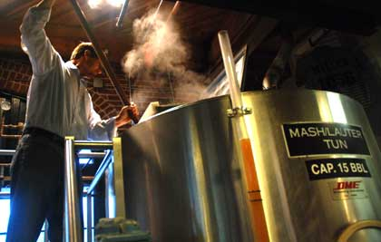James Ottolini stirs fresh hops into mash/lauter tun used as hop back